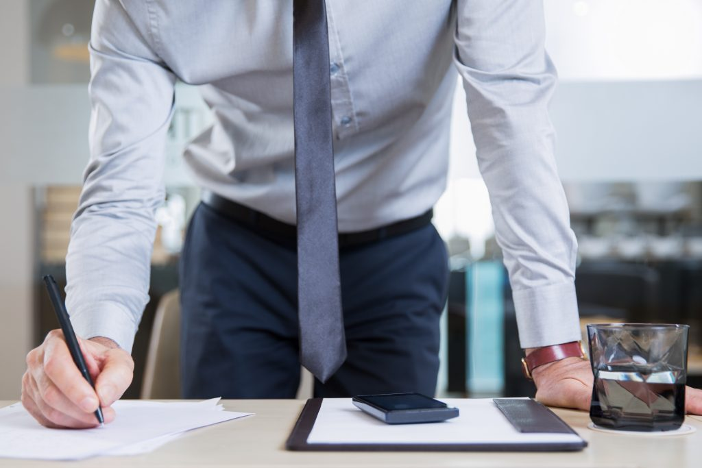 Closeup view of successful businessman wearing shirt and tie, standing near desk in office, signing contract